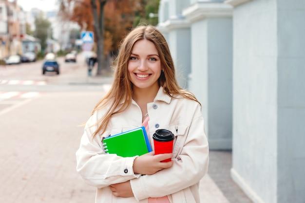 若い女子学生が一杯のコーヒーとノートを持って街を歩きます。白い髪の学生少女 Premium写真
