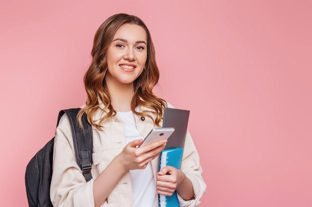 バックパックとメモ帳の白人学生の女の子は、彼女の手とピンクの壁に分離された笑顔で携帯電話を保持しています。テスト試験教育コンセプト。若い女性がスマートフォンでポーズ Premium写真