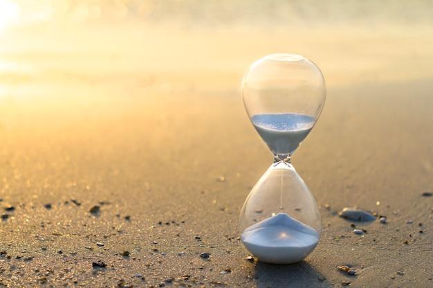 Песочные часы, песок времени в золотом свете Premium Фотографии