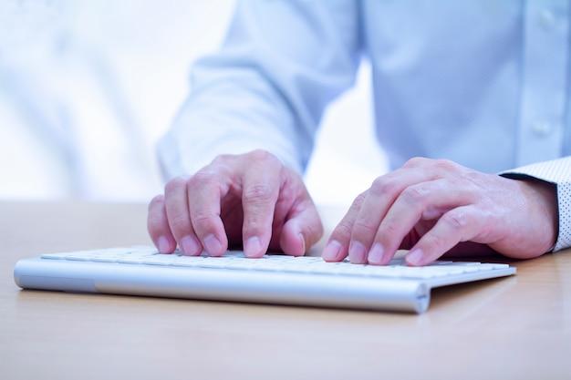 Мужские руки, набрав на современной белой компьютерной клавиатуре Premium Фотографии