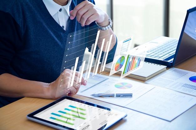 現代のタブレットに未来の仮想画面を拡大するビジネスの男性 Premium写真