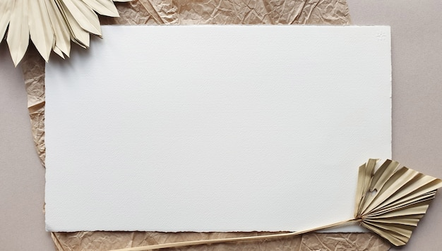織り目加工のテーブル背景に乾燥したヤシの葉で空白の白い結婚式招待状のモックアップ。ブランドアイデンティティのエレガントでモダンなテンプレート。トロピカルなデザイン。フラット横たわっていた、トップビュー Premium写真