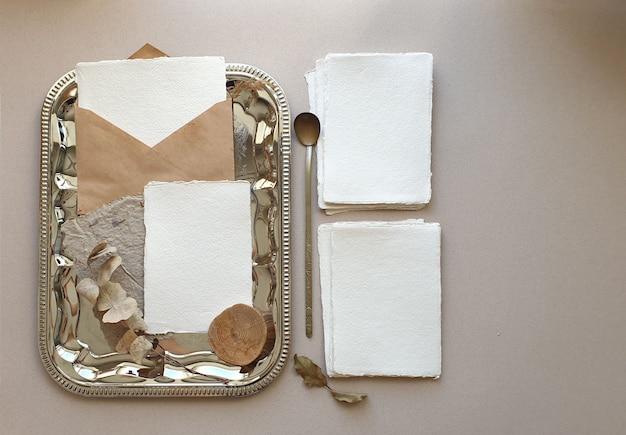 空白の白い結婚式挨拶招待状クラフトエンベロープとモックアップ、ユーカリの葉をテクスチャテーブル背景に残します。ブランドアイデンティティのエレガントでモダンなテンプレート。フラット横たわっていた、トップビュー Premium写真