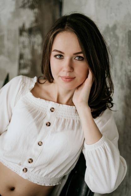短いデニムのショートパンツと椅子に白いブラウスの茶色の髪の少女 Premium写真