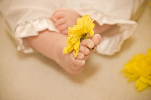 幼児の足。花と赤ちゃんの足 Premium写真