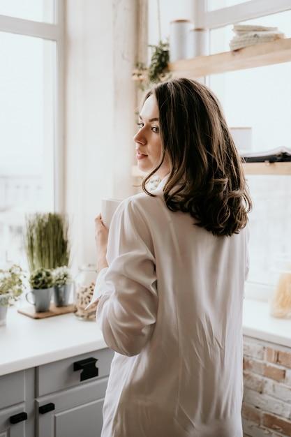 Девушка в белой рубашке пьет кофе по утрам на кухне. Premium Фотографии