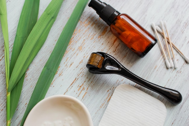 アンチエイジングフェイスクリームの横にあるダーマローラーと美容液美容産業医療用マイクロニードルセラピー用のクローズアップダーマローラー Premium写真