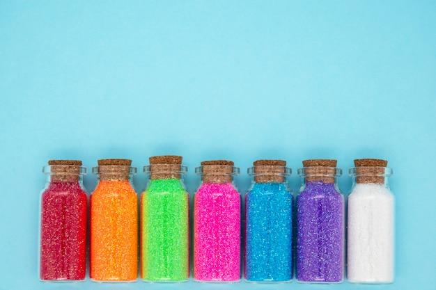 Мода концепция маленьких баночек с красочными конфетти на синей стене Premium Фотографии