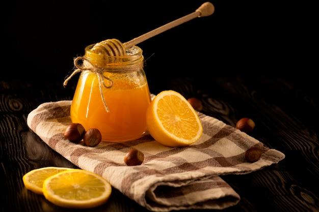 ナッツ、レモン、黒の背景を持つチェックテーブルクロスの上に蜂蜜のスプーンで蜂蜜 Premium写真