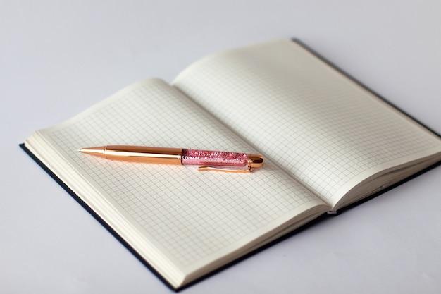 ゴールデンピンクの鮮やかなペンで市松模様のノートのクローズアップ Premium写真