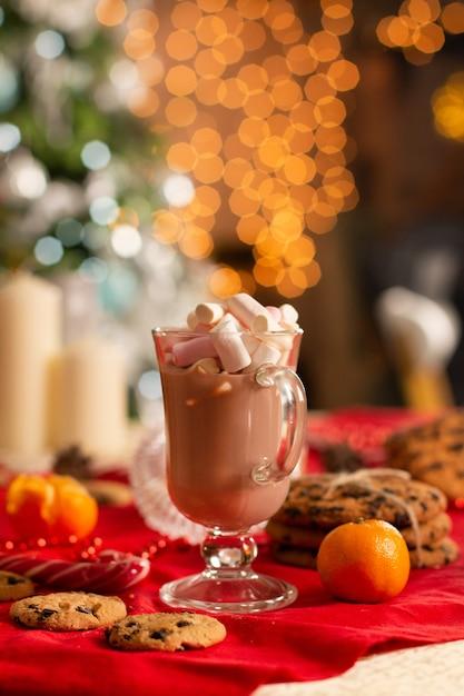 美しい明るい黄色のぼかしとクリスマスツリーの横にある新年のテーブルデコレーション。 Premium写真