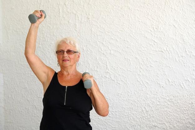 ダンベル体操をしている高齢者の女性 Premium写真