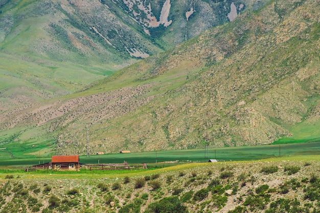 山のふもと近くの絶壁近くの赤い屋根の小さな孤独な村の家。 Premium写真