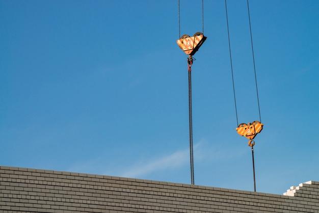 Крюк башенного крана над незаконченным зданием в строительной площадке. фоновое изображение белой кирпичной стены под голубым небом. фоновое изображение процесса строительства. Premium Фотографии