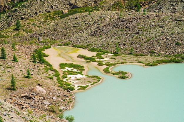 沼地のある山の石の斜面近くの古いターコイズ色の湖。淡い湿地の水の滑らかな表面。白い砂。アルタイ自然の異常な風景。 Premium写真