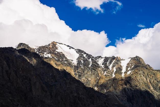 Снег на гигантском скалистом гребне под голубым облачным небом. темный крутой склон горы. удивительная снежная горная цепь в солнечном свете. прекрасные скалы. атмосферный солнечный пейзаж величественной природы высокогорья. Premium Фотографии