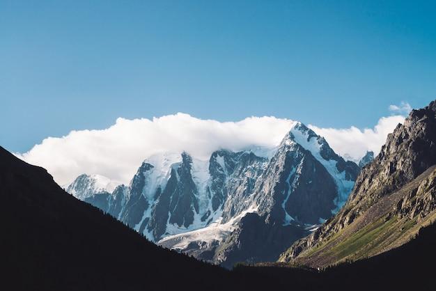 Изумительный ледник под голубым небом. горный хребет со снегом. огромное облако на гигантских чудесных снежных горах. атмосферный минималистичный угрюмый пейзаж величественной природы высокогорья в матовых тонах. Premium Фотографии