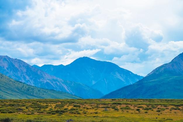 Захватывающий вид гигантских гор под облачным небом. огромный горный хребет в пасмурную погоду. прекрасные дикие пейзажи. атмосферный драматический горный ландшафт величественной природы. живописный горный пейзаж. Premium Фотографии