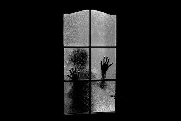 ガラスの後ろの女の子の暗いシルエット。 Premium写真
