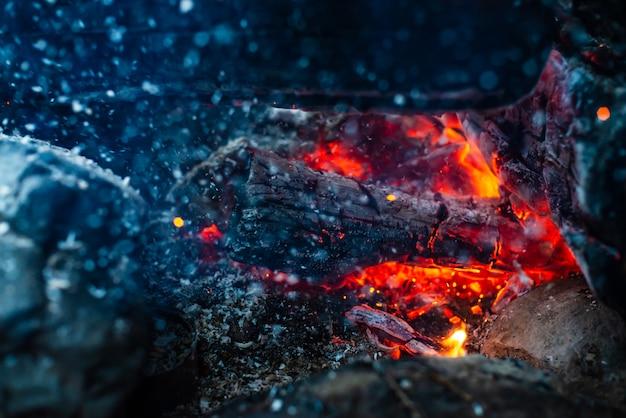 Тлеющие бревна сгорели в ярком огне крупным планом. Premium Фотографии