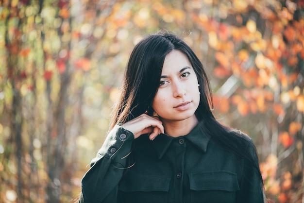 鮮やかな葉に囲まれた女性の美しさの肖像画。 Premium写真