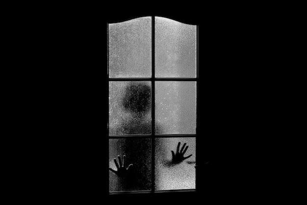Темный силуэт девушки за стеклом. Premium Фотографии