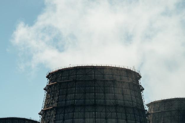 Три большие башни тэц крупным планом. белый пар от широкой трубы тэц на голубом небе. огромные трубы тэс производят пар для электроэнергии. Premium Фотографии