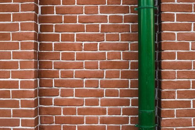緑の縦樋と赤レンガの壁。 Premium写真