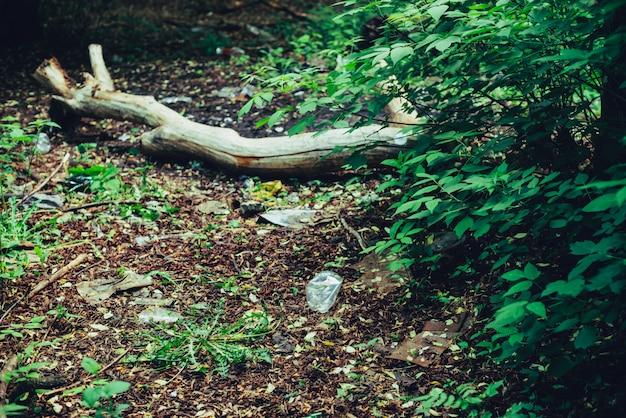 植物の間の森のゴミ山。どこでも自然に有毒プラスチック。植生に囲まれた公園のゴミの山。汚染された土壌。環境汚染。生態学的な問題。ゴミをどこかに捨てます。 Premium写真