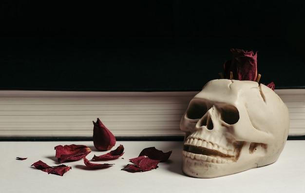 赤い乾燥されたばらと白い背景の上のビンテージスカル灰皿。設計。本。 Premium写真