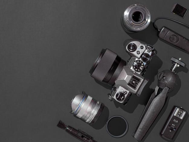 黒の背景にデジタル一眼レフカメラ、レンズ、ペンタブレット、カメラアクセサリーと写真家の職場。カメラ、写真、ビジュアルコンテンツのコンセプト。フラットレイアウトまたはトップビュー。コピースペース。ハードライト。 Premium写真