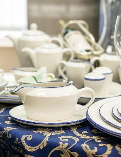 Множество новых блюд заделывают на стол с синей скатерти. блюдце, тарелки, чайники, бутылка вина на столе. неглубоко фо. вертикальный Premium Фотографии
