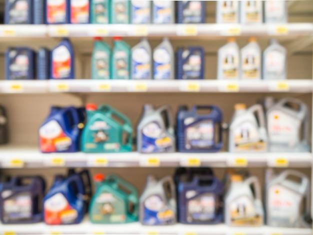 Размытые красочные бутылки моторного масла на полках в супермаркете в качестве фона Premium Фотографии
