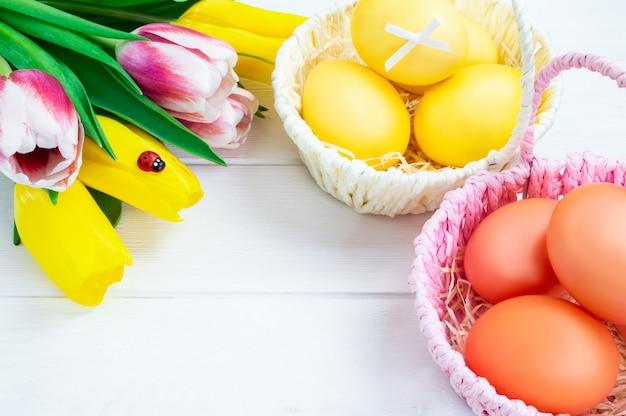 Корзины с красочные пасхальные яйца и букет из тюльпанов на белом фоне деревянные. Premium Фотографии