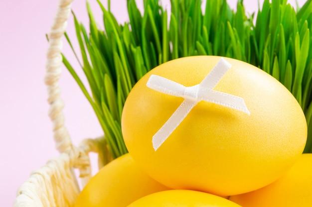 Цветные пасхальные яйца в корзине с декоративной травой. розовый фон концепция праздника пасхи. Premium Фотографии