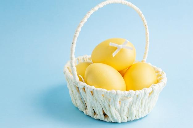 Красочные пасхальные яйца в белой корзине на синем фоне. Premium Фотографии