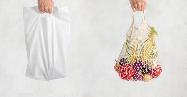 Полиэтиленовый пакет и сетка в руке на белом. покупки без отходов. экологичная одноразовая упаковка Premium Фотографии