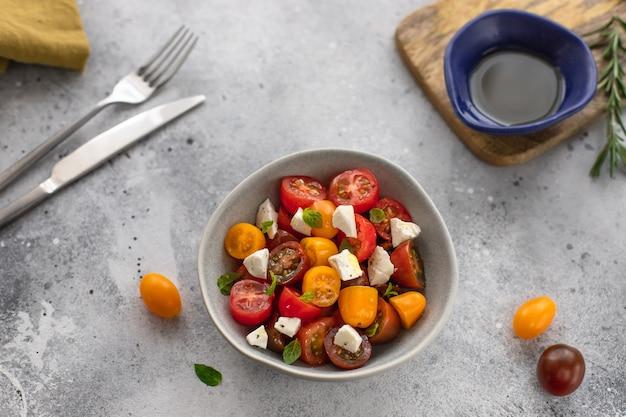 Салат из свежих овощей с сыром фета в миске здоровая пища с большим количеством витаминов серая бетонная поверхность Premium Фотографии