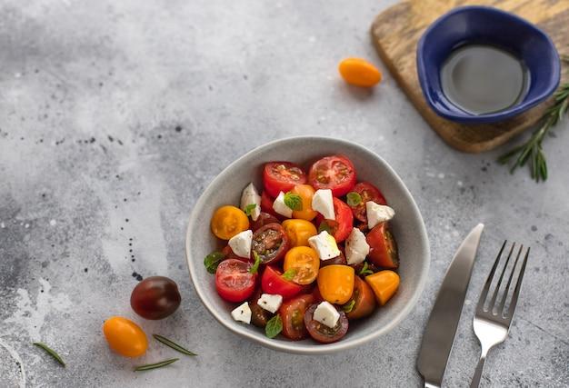 Диетический салат со свежими помидорами черри, сыром фета, розмарином и оливковым маслом вегетарианская здоровая концепция серая бетонная поверхность, Premium Фотографии