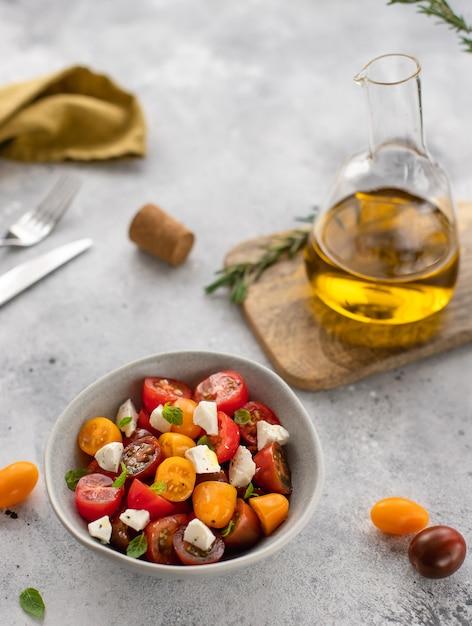 Салат из свежих помидоров, сыра фета, базилика, оливкового масла здоровая пища, диета, серая бетонная поверхность, Premium Фотографии