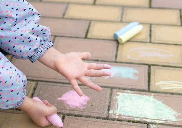 Детская ладонь, окрашенная розовым мелом. рисунок мелом на тротуаре. искусство, творческое воспитание для детей. мягкий фокус Premium Фотографии