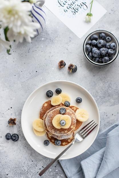 グレーのコンクリート表面に新鮮なブルーベリー、バナナ、粉砂糖を加えたおいしいパンケーキ。垂直方向の画像、上面図、フラットレイアウト Premium写真