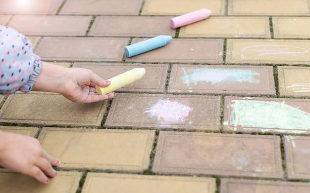 Маленькая девочка выбирает мел для рисования на асфальте, тротуаре. активные детские игры Premium Фотографии