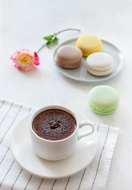 Чашка горячего шоколада с цветами макарунс Premium Фотографии