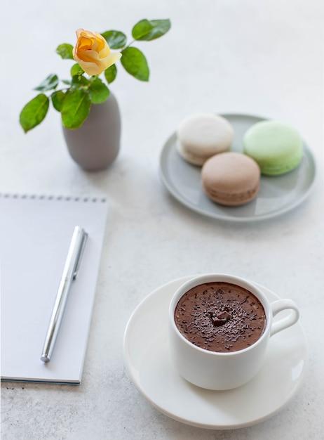Чашка горячего шоколада с цветами макарунс и блокнотом Premium Фотографии