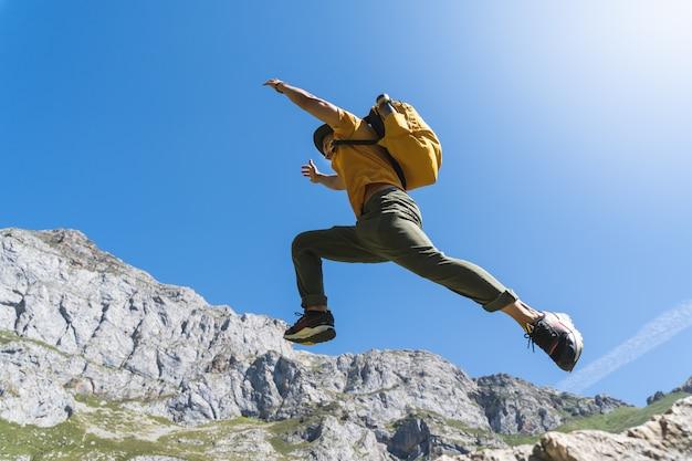ハンサムな若い男が山でジャンプします。 Premium写真