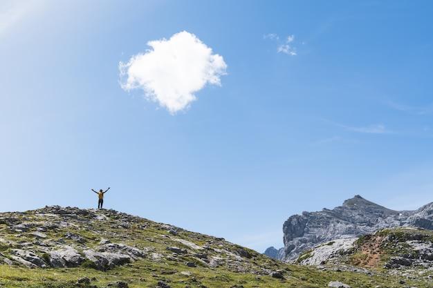 Молодой человек руки вверх на вершине горы. Premium Фотографии