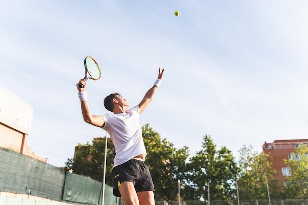 Молодой человек, играя в теннис на открытом воздухе. Premium Фотографии
