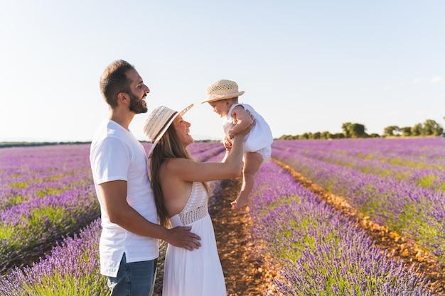 Счастливая семья весело в поле цветов. Premium Фотографии