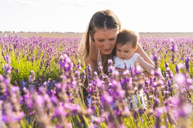 Мать и ребенок с удовольствием в поле цветов. Premium Фотографии